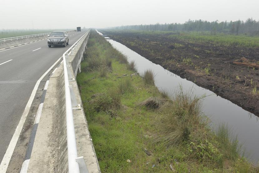 Kendaraan melintas di samping sekat kanal lahan gambut di Jembatan Tumbang Nusa, Kalteng, Kamis (29/10). Sekat kanal dengan total panjang 9,5 km tersebut dibuat untuk mencegah terjadinya kebakaran lahan gambut di sekitar tempat itu. ANTARA/Saptono/Spt/15