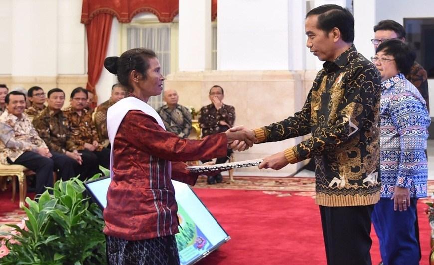 Presiden Jokowi didampingi menteri lingkungan hidup dan kehutanan Siti Nurbaya, menteri dalam negeri, Cahyo Kumolo menyerahkan SK hutan adat kepada Indolaku perwakilan komunitas adat Wana Posangke, Sulteng