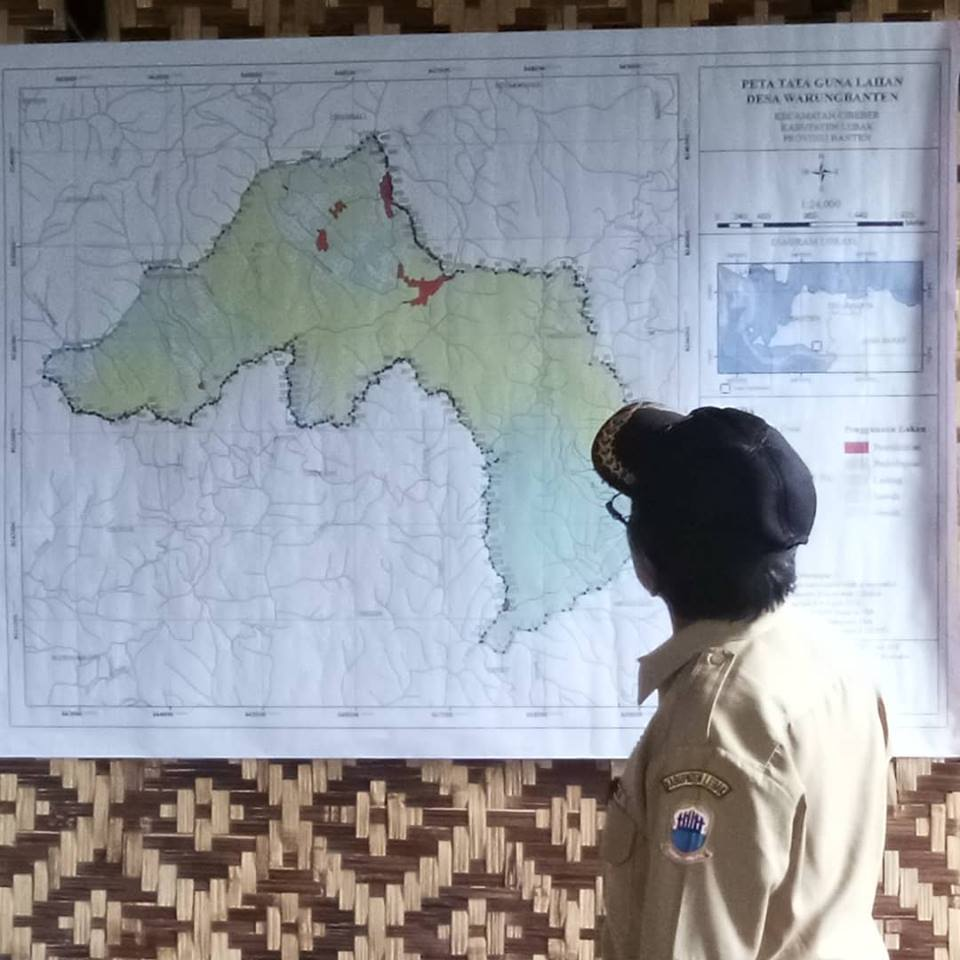 Amil Sarto Paipto, Perangkat Desa Warungbanten, Kec. Cibeber, Kab. Lebak, Banten sedang memperhatikan peta tata guna lahan Desa Warungbanten pada Selasa (31/7/2018) sore di Imah Gede Kaolotan Cibadak